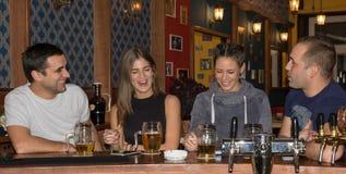 Amigos que tienen bebidas en una barra imagenes de archivo