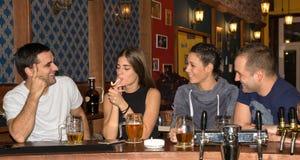 Amigos que tienen bebidas en una barra foto de archivo libre de regalías