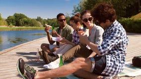 Amigos que tienen comida campestre en el embarcadero del lago almacen de metraje de vídeo