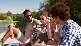 Amigos que tienen comida campestre en el embarcadero en el lago o el río almacen de video