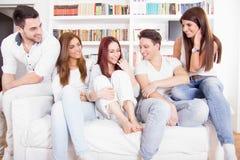 Amigos que tienen conversación sobre el sofá en casa Imagen de archivo