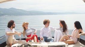 Amigos que tienen navegación de la diversión en un yate en el mar, la risa, la charla y la refrigeración metrajes