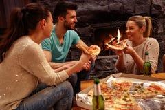 Amigos que tienen tiempo de la diversión junto en casa y que comen la pizza Foto de archivo
