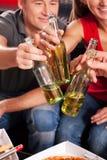 Amigos que tienen un partido y que tintinean las botellas Fotos de archivo