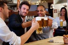 Amigos que tintinean con las tazas de cerveza en pub Fotos de archivo libres de regalías