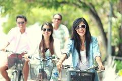 Amigos que têm a bicicleta da equitação do divertimento junto Fotografia de Stock