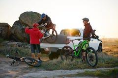 Amigos que tomam bicicletas de MTB fora do caminhão Offroad do recolhimento nas montanhas no por do sol Conceito da aventura e do foto de stock