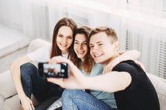 Amigos que tomam o selfie do grupo no smartphone imagem de stock