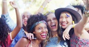 Amigos que toman el selfie con el teléfono móvil en el festival de música 4k