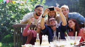 Amigos que toman el selfie en el partido en jardín del verano almacen de video