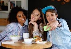 Amigos que toman el selfie en un café Imagen de archivo