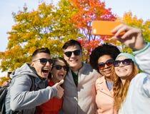 Amigos que toman el selfie por smartphone en parque del otoño fotos de archivo
