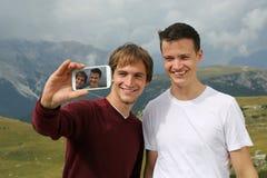 Amigos que toman imágenes con un smartphone el día de fiesta Foto de archivo libre de regalías