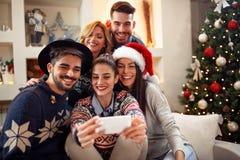 Amigos que toman la foto con el teléfono móvil para la Navidad foto de archivo libre de regalías
