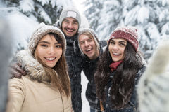 Amigos que toman la nieve Forest Young People Group Outdoor de la sonrisa de la foto de Selfie Fotos de archivo libres de regalías