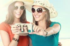 Amigos que toman las fotos con un smartphone Foto de archivo libre de regalías