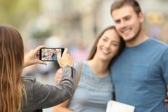 Amigos que toman las fotos con un teléfono elegante en la calle Fotografía de archivo libre de regalías