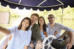 Amigos que toman Selfie durante paseo del barco en el río junto imagen de archivo