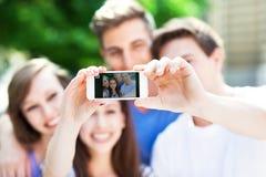 Amigos que toman un selfie con smartphone Foto de archivo libre de regalías