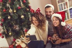 Amigos que toman un selfie de la mañana de la Navidad foto de archivo