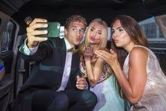 Amigos que toman un selfie en la parte posterior de una limusina Foto de archivo