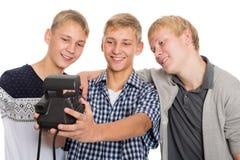 Amigos que toman a uno mismo en la impresión inmediata de la cámara vieja Fotografía de archivo