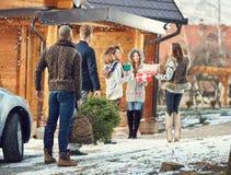 Amigos que traen el árbol de navidad y los regalos en casa imagen de archivo