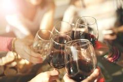 Amigos que tuestan con el vino imágenes de archivo libres de regalías