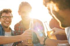 Amigos que tuestan con la cerveza Imagen de archivo libre de regalías