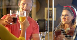 Amigos que tuestan el vidrio de cerveza en la fábrica 4k de la cervecería metrajes