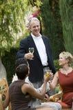 Amigos que tuestan las copas de vino en jardín Imágenes de archivo libres de regalías