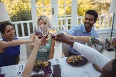 Amigos que tuestan las copas de vino en restaurante Imagenes de archivo
