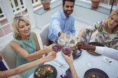 Amigos que tuestan las copas de vino en restaurante Fotografía de archivo