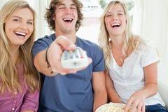 Amigos que usam o telecontrole para trabalhar a tevê como riem Foto de Stock