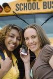 Amigos que usan el teléfono celular en autobús escolar Fotografía de archivo
