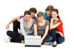 Amigos que usan la computadora portátil Imagen de archivo libre de regalías
