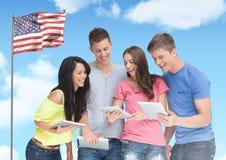 Amigos que usan la tableta digital contra bandera americana en fondo Foto de archivo