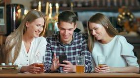 Amigos que usan los smartphones que se sientan en el café almacen de video