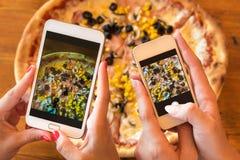 Amigos que usan smartphones para tomar las fotos de su pizza foto de archivo