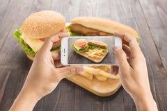 Amigos que usan smartphones para tomar las fotos del perrito caliente y del hamburge Foto de archivo