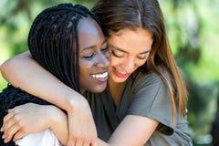 Amigos raciales diversos que abrazan al aire libre Fotos de archivo libres de regalías