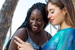 Amigos raciales diversos que miran el teléfono elegante Fotografía de archivo