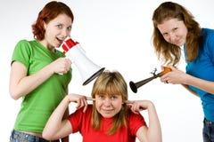 Amigos ruidosos que incomodan a la muchacha Fotos de archivo