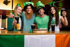 Amigos sonrientes con el accesorio irlandés Imagenes de archivo