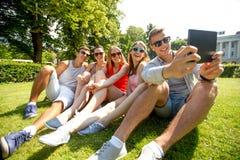 Amigos sonrientes con el ordenador de la PC de la tableta en parque Imagen de archivo libre de regalías