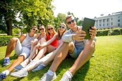 Amigos sonrientes con el ordenador de la PC de la tableta en parque Foto de archivo