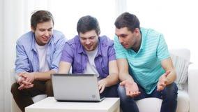 Amigos sonrientes con el ordenador portátil en casa metrajes