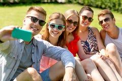 Amigos sonrientes con el smartphone que se sienta en hierba Imagen de archivo