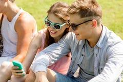 Amigos sonrientes con el smartphone que se sienta en parque Fotos de archivo libres de regalías