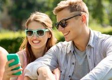 Amigos sonrientes con el smartphone que se sienta en parque Imagen de archivo libre de regalías